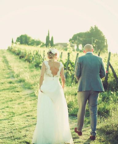 Bruidspaar loopt samen door wijngaard bij hun Italiaanse bruiloft in Nederland